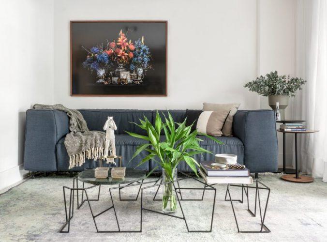 Sofá cinza, tapete cinza, mesa de centro em ferro e quadro com fundo preto e flores