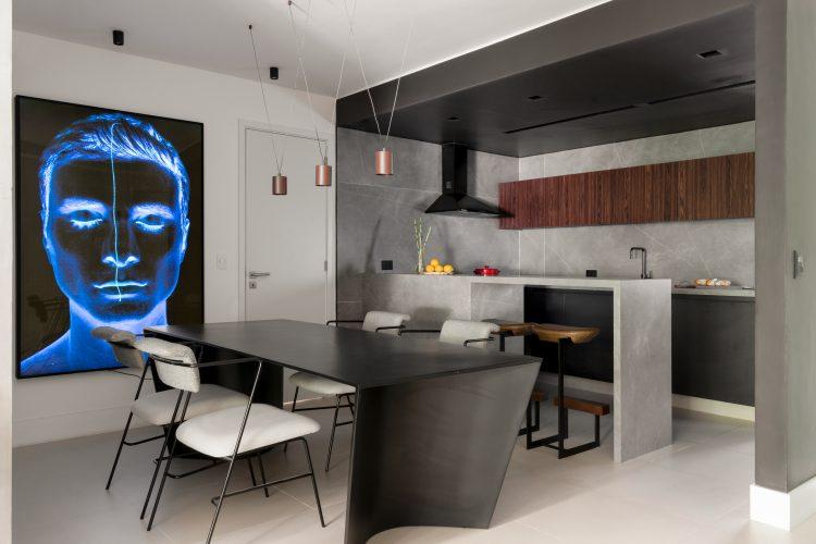 Quadro com um rosto azul, mesa de jantar preta , bancada da cozinha aberta para a sala em cimento