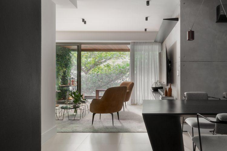Apartamento no Leblon com décor minimalista e brutalista. Sala com varanda e cortina em linho branco. mesa preta
