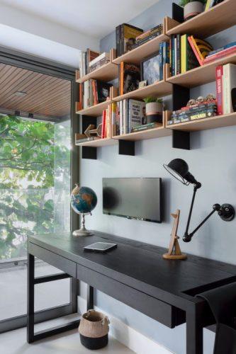 Escrevaninha preta com nicho em madeira em cima com livros, monitor e luminaria na parede