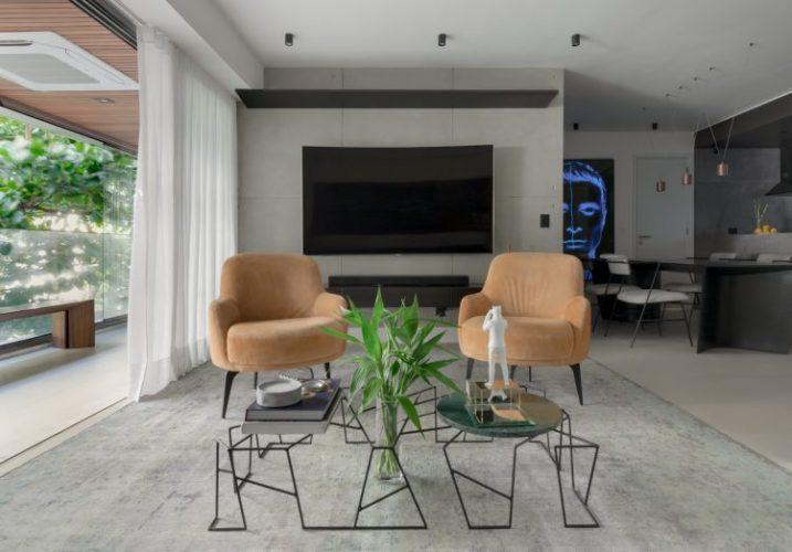 Apartamento no Leblon com décor minimalista e brutalista. Tapete cinza , paredes em concreto, mesa de centro em ferro e tv na parede