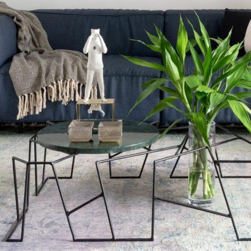 Mesa de centro em ferro e tampo pequeno redondo em pedra. Vaso com bambu da sorte em cima de tapete cinza
