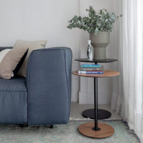 Apartamento no Leblon com décor minimalista e brutalista. Sofá azul acinzentado com duas mesinhas laterias redondas em madeira