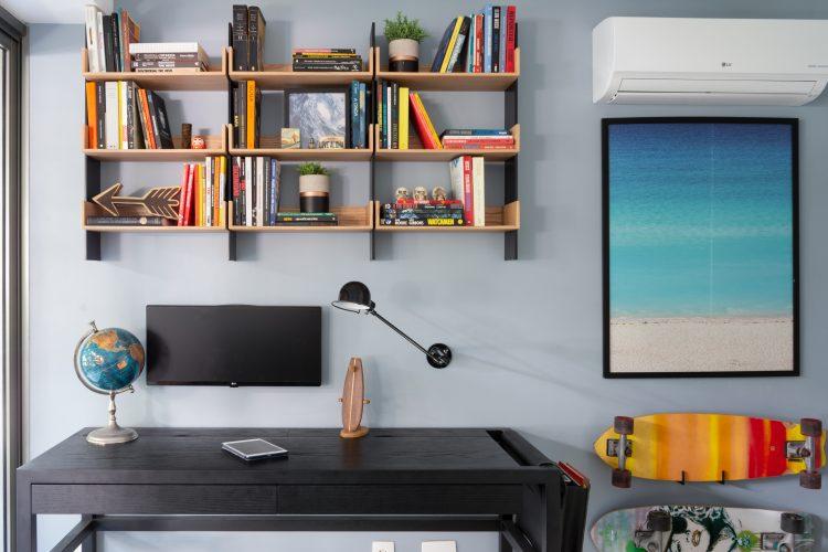 Mesa de escritorio preta, nichos em madeira em cima com livros, monitor e luminaria na parede