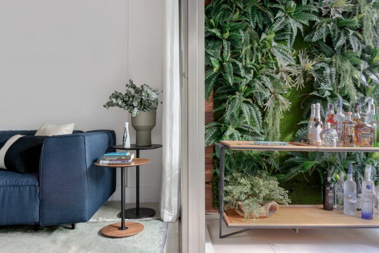 Varanda com parede verde com esuqadria que separa da sala