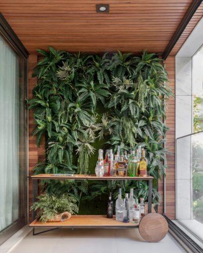Parede verde na varanda e em frente um carrinho de chá arrumado como bar . Teto com ripas em madeira
