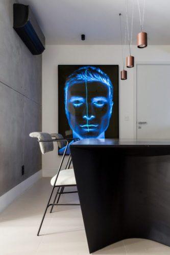 Parede em cimento, quadro com um rosto azul na parede ao lado e mesa preta