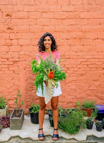 Foto da chef de cozinha Bela Gil, mulher segurando um arranjo de legumes . Bermuda branca, camiseta rosa e atars uma parede de tijolinho