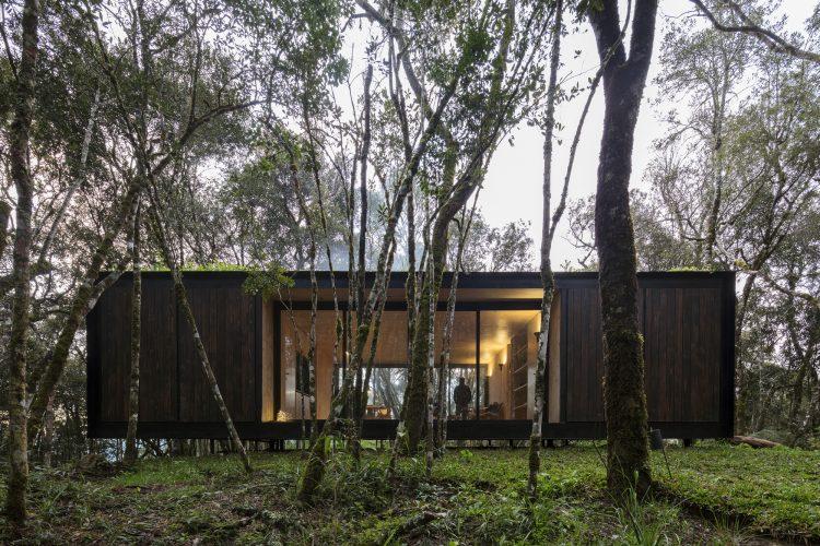 Casas Modulares, sistemas pré-fabricados. Volume retangular preto, com janelas no vão do meio e instalada na mata atlantica