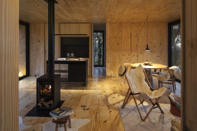 Casas Modulares, sistemas pré-fabricados . Ambiente de estar todo em madeira. piso, paredes e teto. Com uma mini lareira