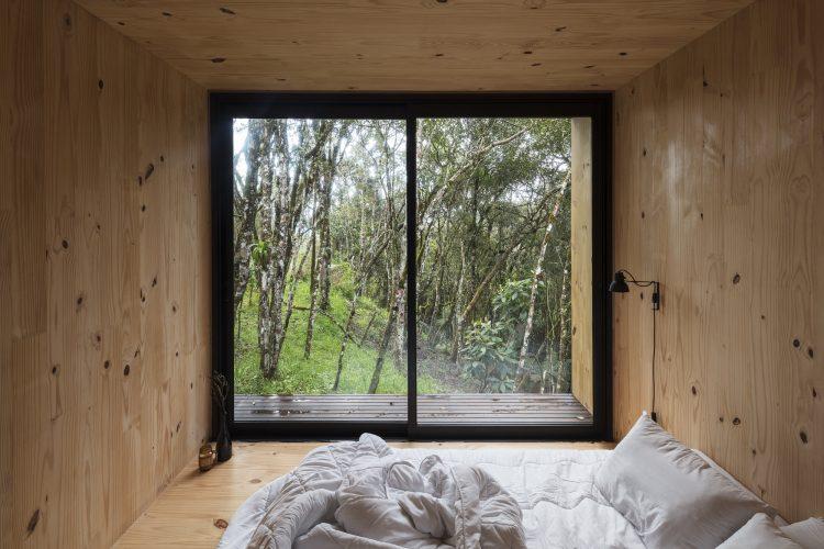 Casas Modulares, sistemas pré-fabricados . Paredes, piso e teto forrado em madeira e na parede de fundo janelas