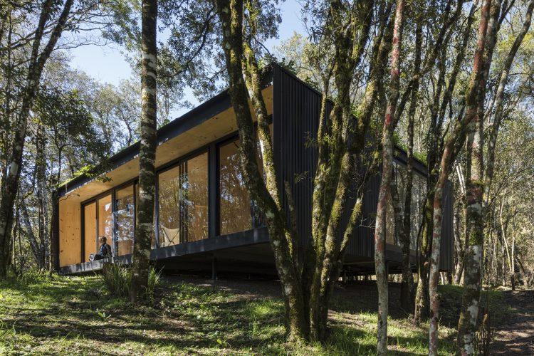 Casas Modulares, sistemas pré-fabricados, Um volume preto com janelas e varada em meio a mata atlantica