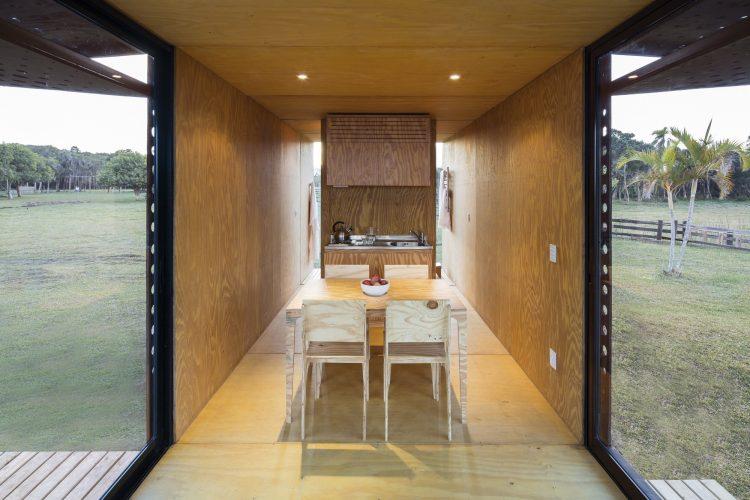 sistemas pré-fabricados. Interior de uma casa pré fabricada. Estreita, todo forrado de madeira e uma mesa no meio