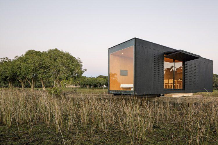 Casas Modulares, um volume preto, com janelas e no meio do campo