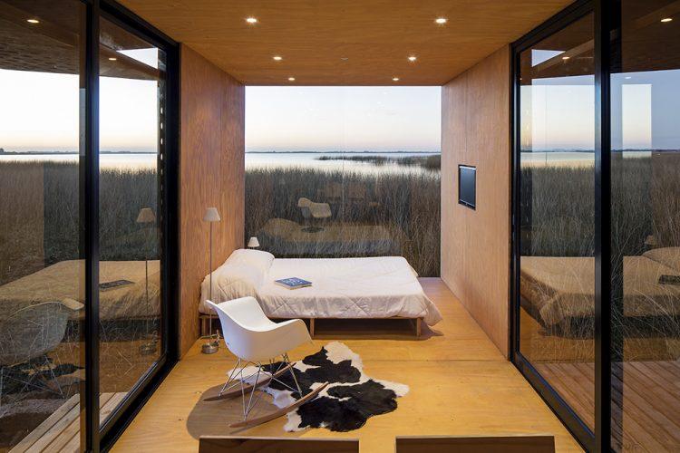 Casas Modulares, sistemas pré-fabricados. Ambiente de um qaurto com janelas em quase todas as paredes. Cama branca e em frente uma parede em madeira com tv