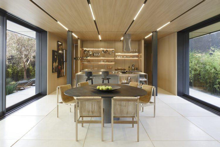 Casas Modulares, sistemas pré-fabricados. Teto revestido em madeira, aberto nas laterais e uma mesa redonda e uma cozinha oa fundo