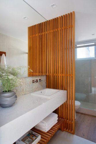 Banheiro com branca e divisoria em madeira ripada
