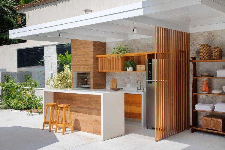 Cozinha na area externa, bancada, churrasqueira e uma divisoria ripada em madeira
