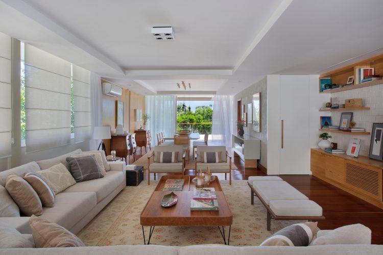 sala ampla e clara com moveis em tom de bege, mesa de centro em madeira