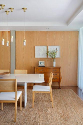 sala de jantar com mesa branca, parede revestida em madeira com uma comoda antiga na frente