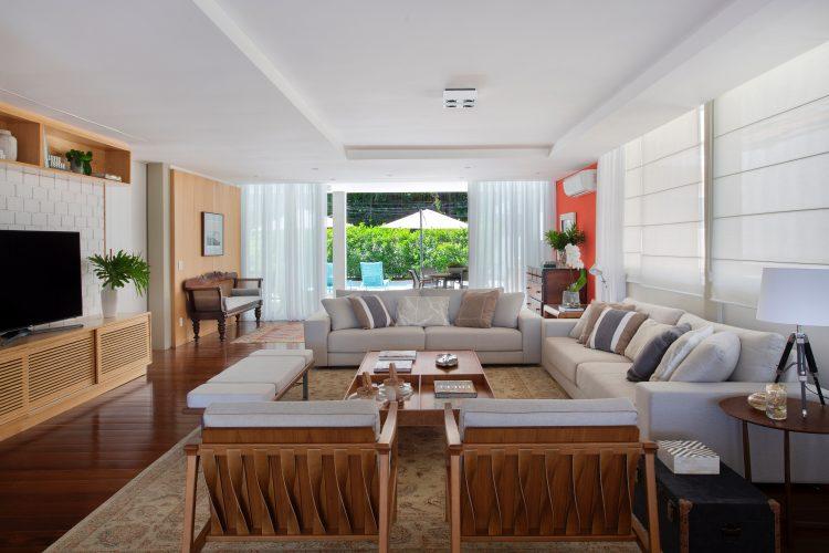 sala ampla e clara. cortina brancas. sofá claro e aparador embaixo da tv em madeira