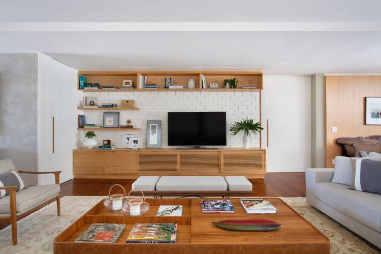mesa de centro em madeira. Parede em frente ao sofá de tijolinho branco, com prateleiras e movel para a tv em madeira