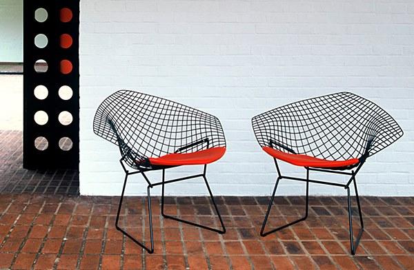 Duas cadeiras em metal tramado na ocr preta com assento em almofada vermelha
