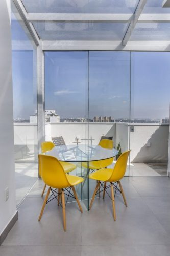 Cobertura em um aparatmento com esquadria de vidro , um amesa redonda e cadeira amarelas