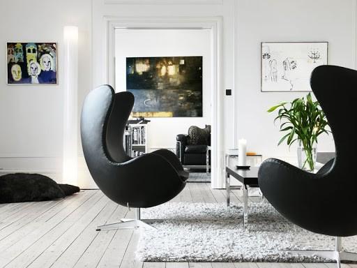 seleção de 10 cadeiras icônicas do design, Egg Chair. Poltrona grande na cor preta em uma sala toda branca