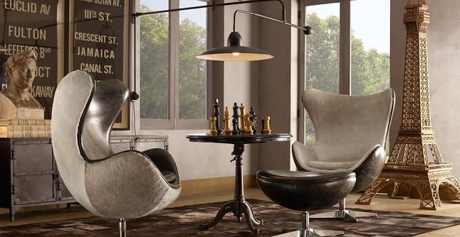 seleção de 10 cadeiras icônicas do design, Egg Chair. Duas poltronas na cor bege, grandes e uma mesa redonda com jogo de xadrez no meio