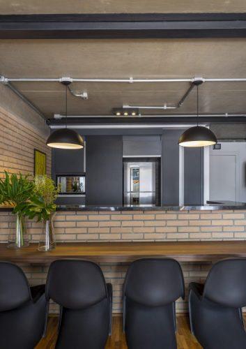 Cozinha gourmet, bancada em tijolhinhos, banavada em madeira e armarios pretos com cadeira pretas