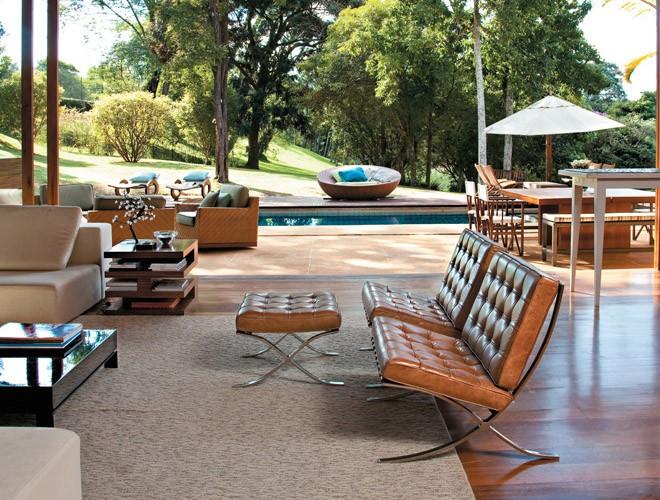Cadeira barcelona em couro marrom, peça clássica do design. Sala aberta para a area externa.