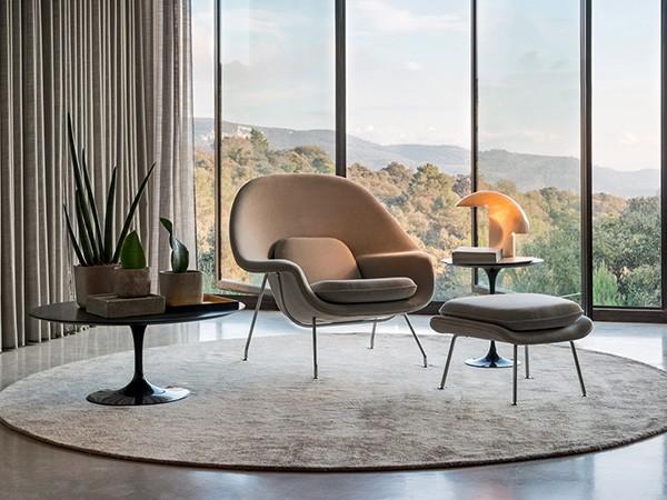 seleção de 10 cadeiras icônicas do design, WOMB. Sala com vidros do teto ao chão com vistas de montanha, um poltrona bege em cima de uma tapete redondo