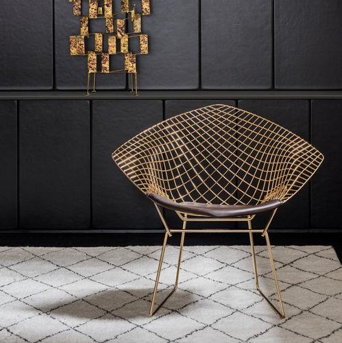 seleção de 10 cadeiras icônicas do design, cadeira Diamond. Trama em metal dourado com aprede preta ao fundo