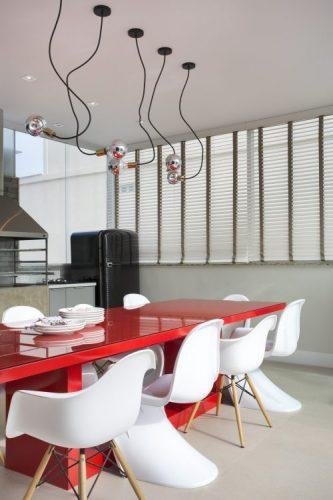 Mesa vermelha com cadeiras na cor branca