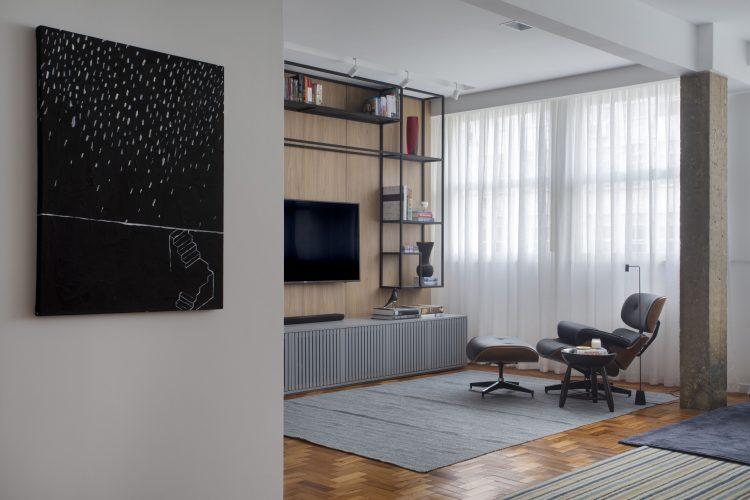 seleção de 10 cadeiras icônicas do design, EAMES LOUNGE . Poltrona preta em couro em um sala de tv