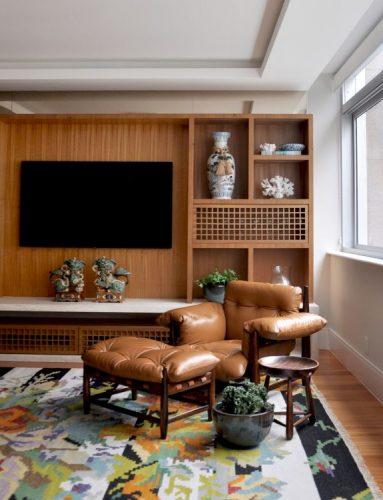 seleção de 10 cadeiras icônicas do design, Poltrona Mole. Poltrona em couro e madeira em uma sala de tv com painel em madeira