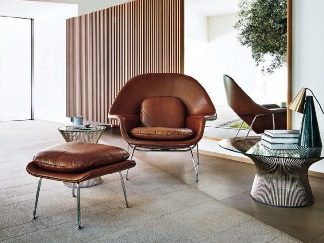 seleção de 10 cadeiras icônicas do design, WOMB .Poltrona em couro marrom com puff na frete em um ambinete claro de uma sala so com ela