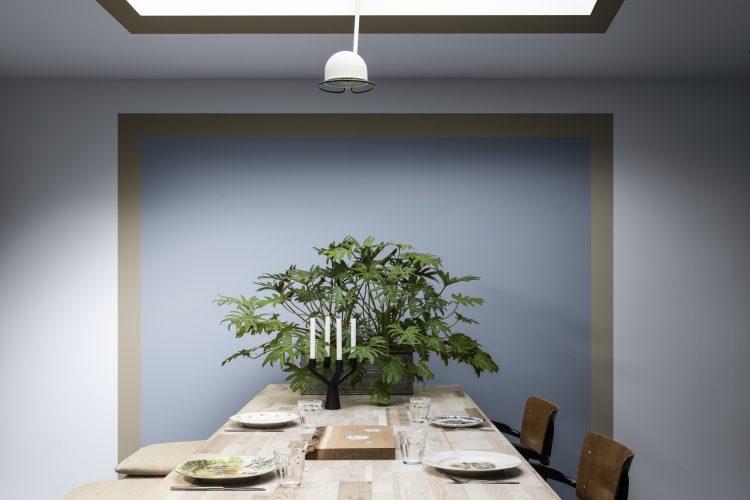 Pedra Esculpida é a Cor do Ano da Coral para 2021. Parede de fundo de uma mesa de jantar, pinrada com um quadrado aul, uma barra bege em volta dele e a parede cinza clarinho