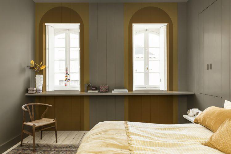 Pedra Esculpida é a Cor do Ano da Coral para 2021. Em um quarto, duas janelas brancas e em cima arcos pintados de amarelo