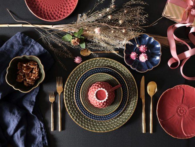 Foto vista de cima de uma mesa posta, tampo da mesa preto, louças rosa e verde com um arranjo de flor sempre viva no meio