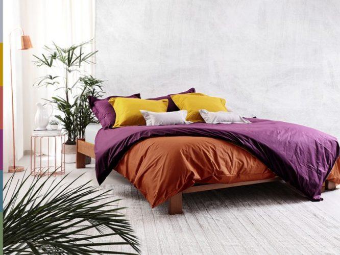 Cama com lençol colorido, colocada invesada em um quarto branco