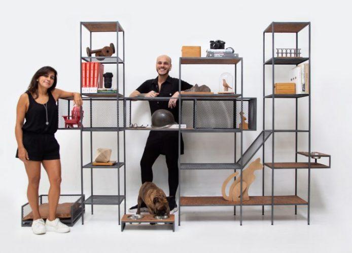 Foto de uma mulher e um homem, com uma estante modular em ferro e um bulldog