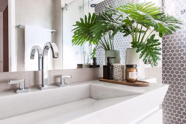Banheiro com bancada em marmore branco e parede do chuveiro com revestimento hexágono na cor preta