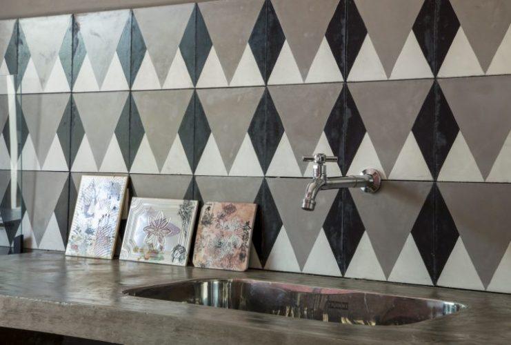 Paredes geometricas, revestida com azulejo triangulo cinza em cima da bancada da cozinha