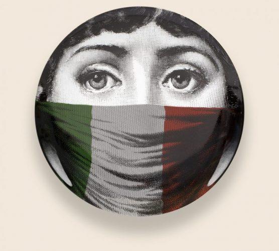 Prato de porcelana da marca Fornasetti com um rosto estampado a e boca coberta com a bandeira da Italia