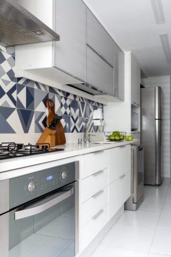cozinha tipo corredor , com aramarios brancos e no frontão azulejos graficos azuis