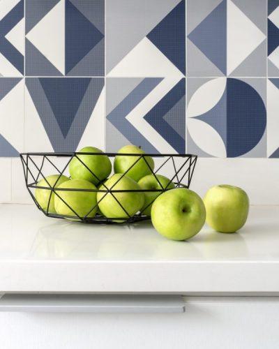 Bancada branca, cesto de fritas com maçã verde e azulejos azuis na parede