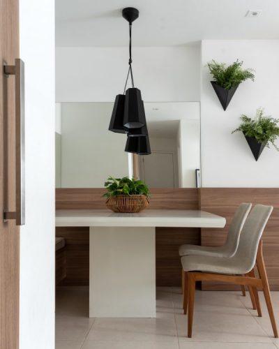 Mesa de jantar branca enconstada na parede que tem metade com espelho