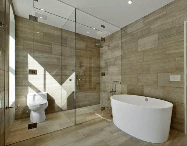 Banheiro grande e claro. Com piso e parede com ao mesmo revestimento imitando madeira, banheira branca e vidro separando a area do box e vaso sanitario
